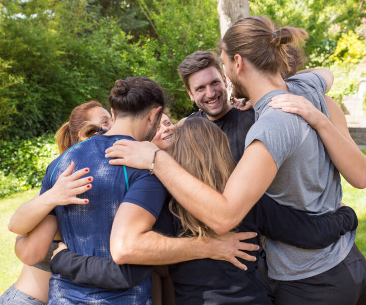 Corporate team spending weekend together outdoors. Men and women in casual forming circle and hugging in park. Corporate teambuilding concept